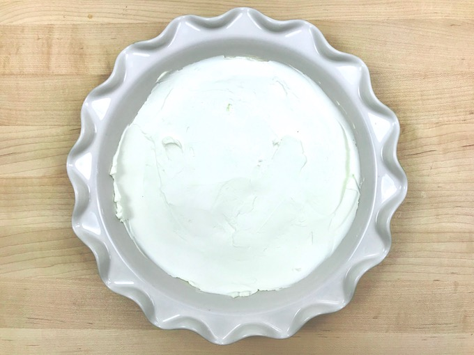 Cream cheese spread on bottom of pie dish for taco dip.