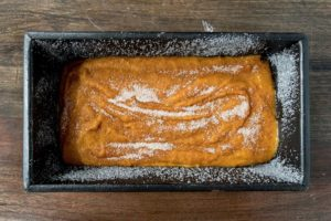 Pumpkin bread batter in pan sprinkled with sugar.