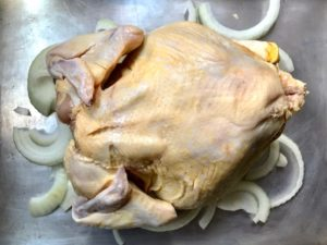 Roasting chicken with wings tucked back.