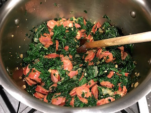 Sautéing kale with linguisa, onions, and garlic.