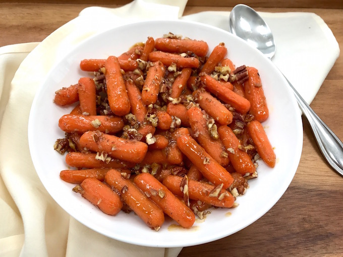Baby carrots with pecans in serving bowl with spoon.