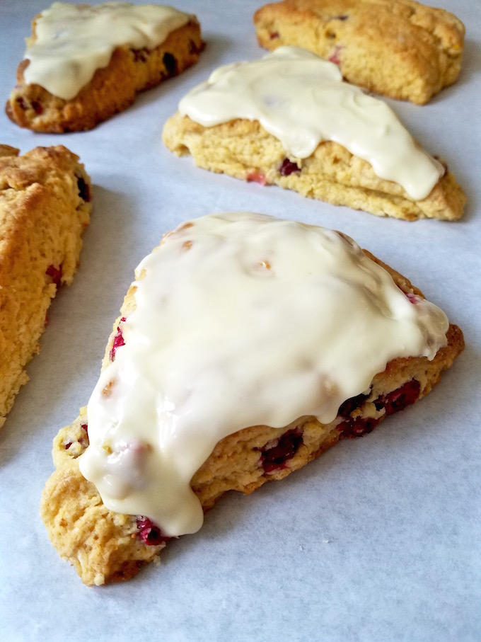 Cranberry orange scone with fresh berries, frosted.