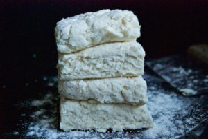 Stacking dough to create layer for buttermilk biscuits.