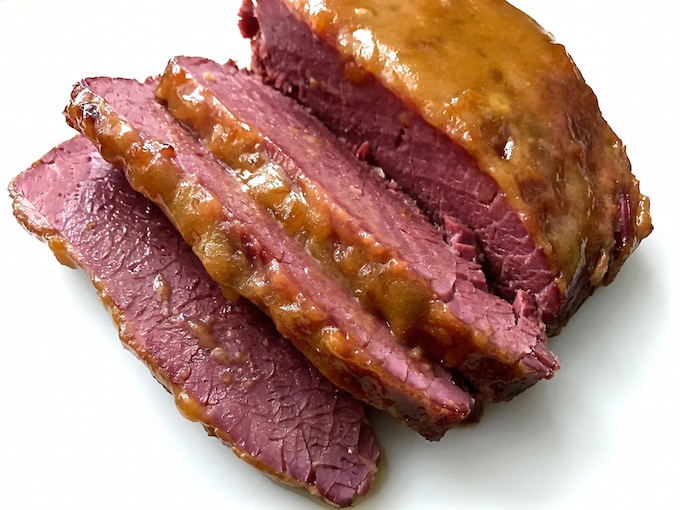 Sliced corned beef topped with apricot and mustard sauce.