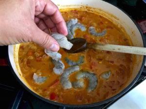 Adding shrimp to sauce.