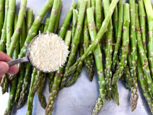 Adding Parmesan to asparagus.