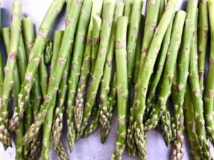 Raw asparagus on baking sheet.