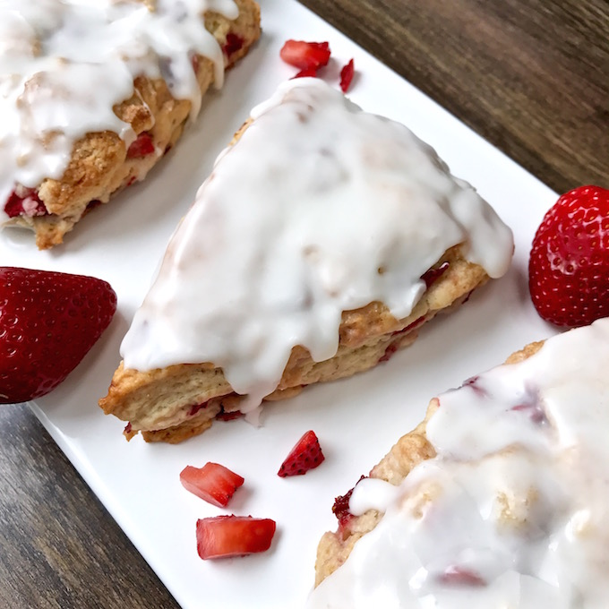 Frosted strawberry scone on plate.