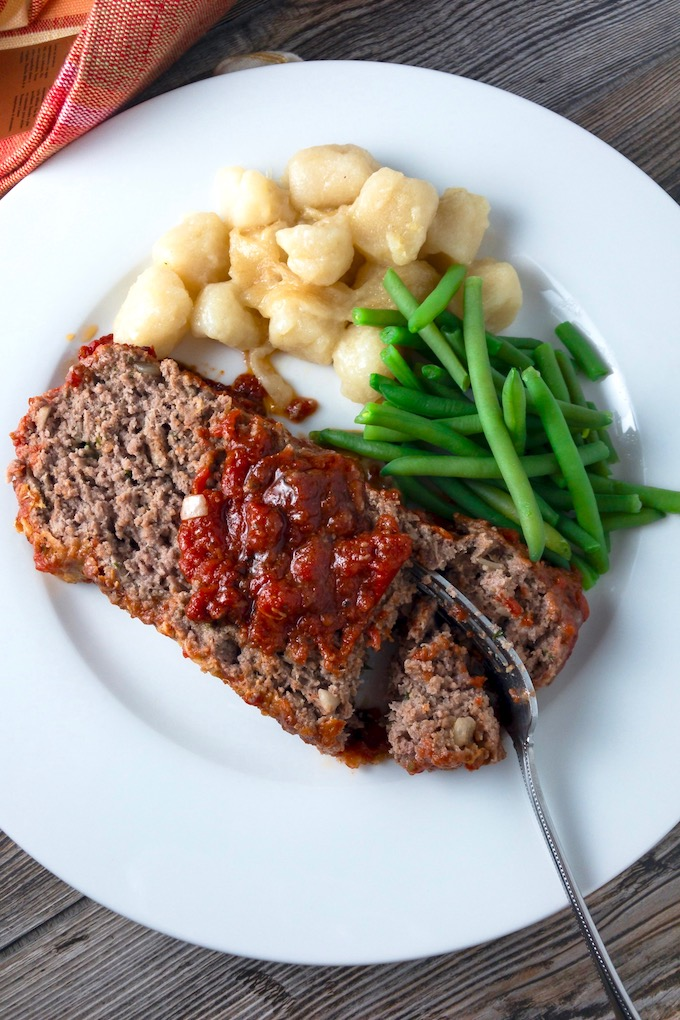 A slice of Italian meatloaf on a plate with sides.