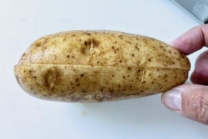 Slicing a potato in half.