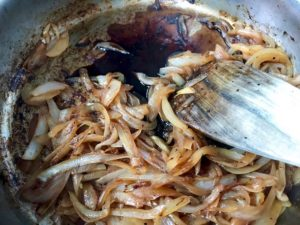 Adding balsamic vinegar to caramelized onions in pan.