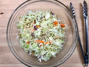 Adding coleslaw mix to the dressing.