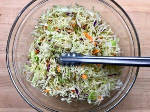 Tossing the coleslaw.