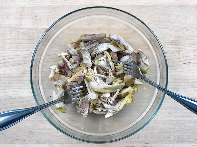 Cooked chicken shredded with two forks in a bowl.