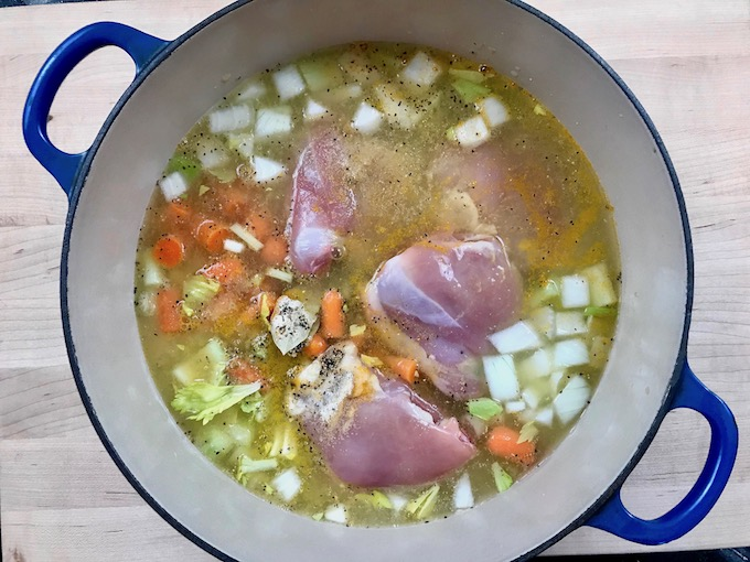 Ingredients for chicken and rice soup in a pot.