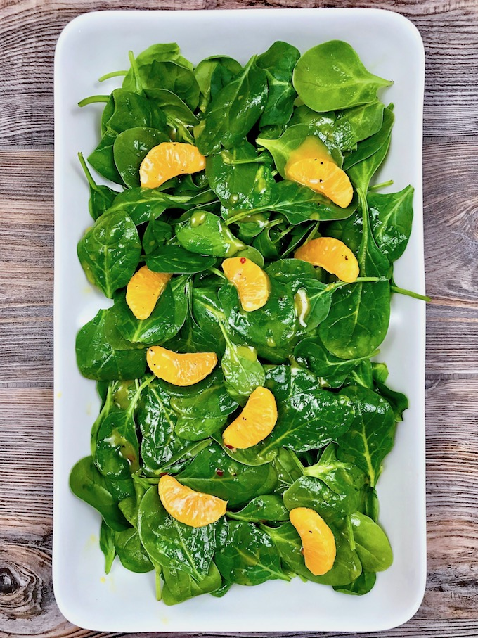 A platter of spinach and clementines drizzled with orange vinaigrette.