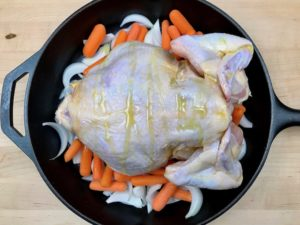 Drizzling underside of chicken with olive oil.