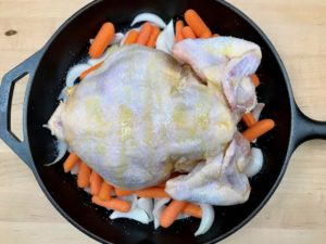 Salting underside of chicken with olive oil.