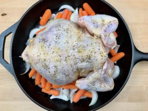 Adding pepper to underside of chicken with olive oil.