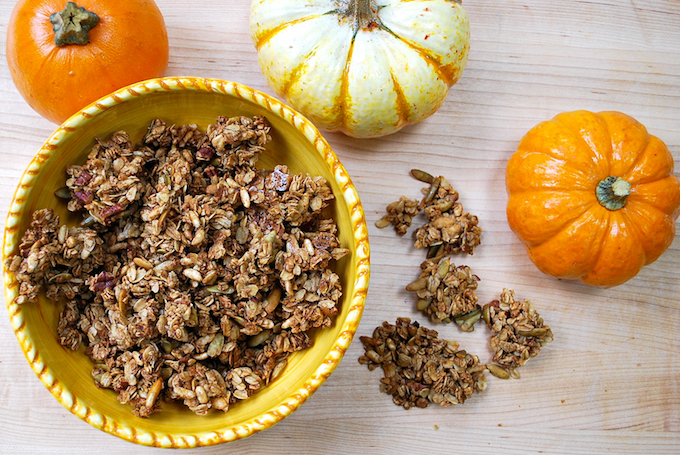 A bowl of pumpkin spice granola surrounded by mini pumpkins.