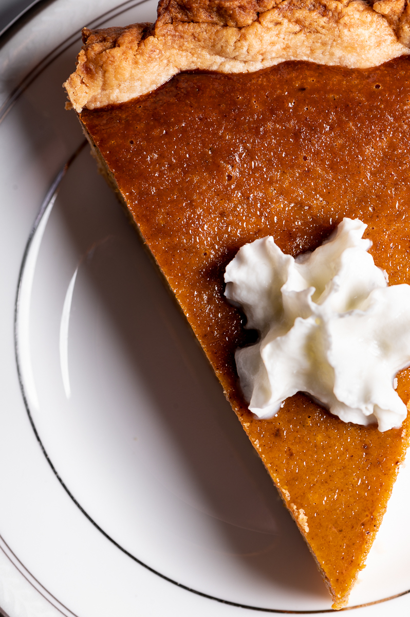 Top view of a slice of pumpkin pie with whipped cream on a white plate.