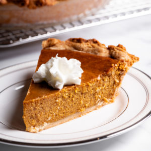 A slice of pumpkin pie with whipped cream on a white plate.