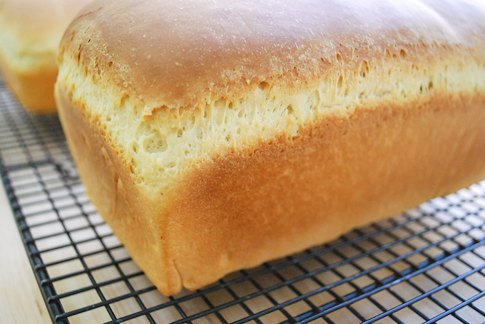 A loaf of bread cooling on a rack.