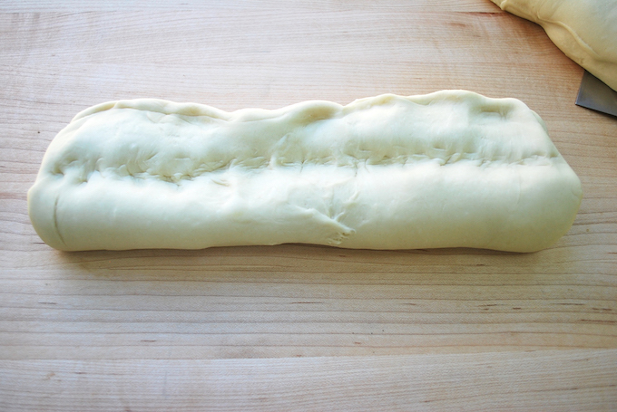 Indenting the log of dough.