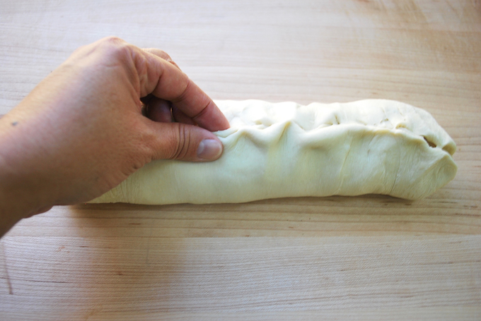 Pinching the seam of the dough together.