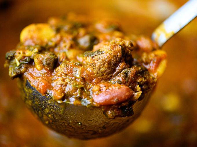 A closeup of a ladle of hearty hamburger soup.