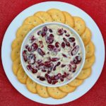 A bowl of New England bean dip surrounded by crackers.