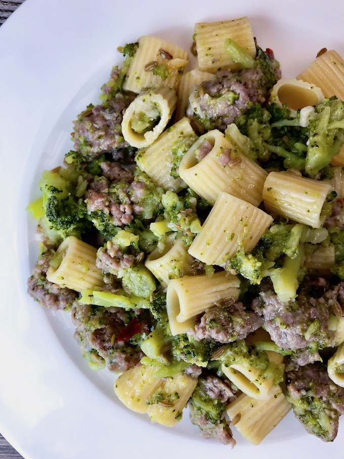 A plate of sausage broccoli and pasta.