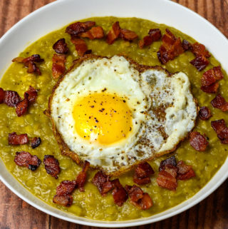 A bowl of split pea soup with a fried egg on top with bacon bits.