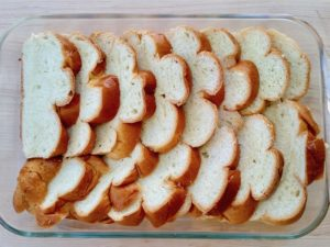 Sliced Challah bread layered in a baking dish.