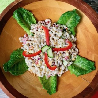A bowl of macaroni salad garnished with red peppers and lettuce leaves.