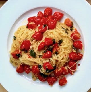 A plate of angel hair pasta with sautéed tomatoes.