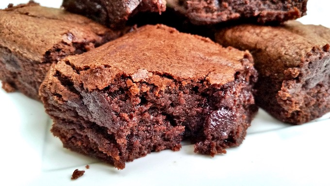 Close up of a cocoa brownie with a bite taken off.