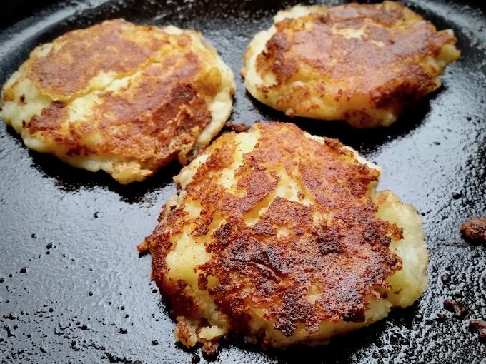 Potato pancakes frying in a cast iron pan.