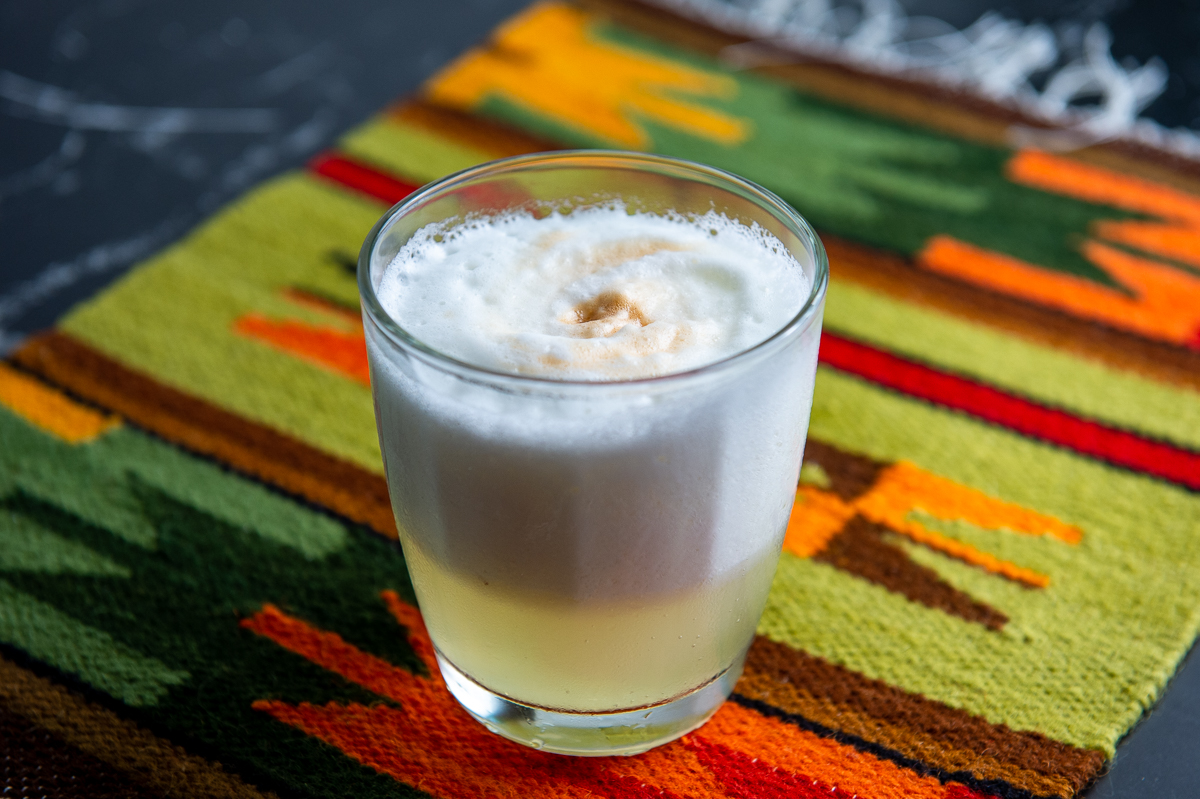 A glass of Peruvian pisco sour on a Peruvian placemat.