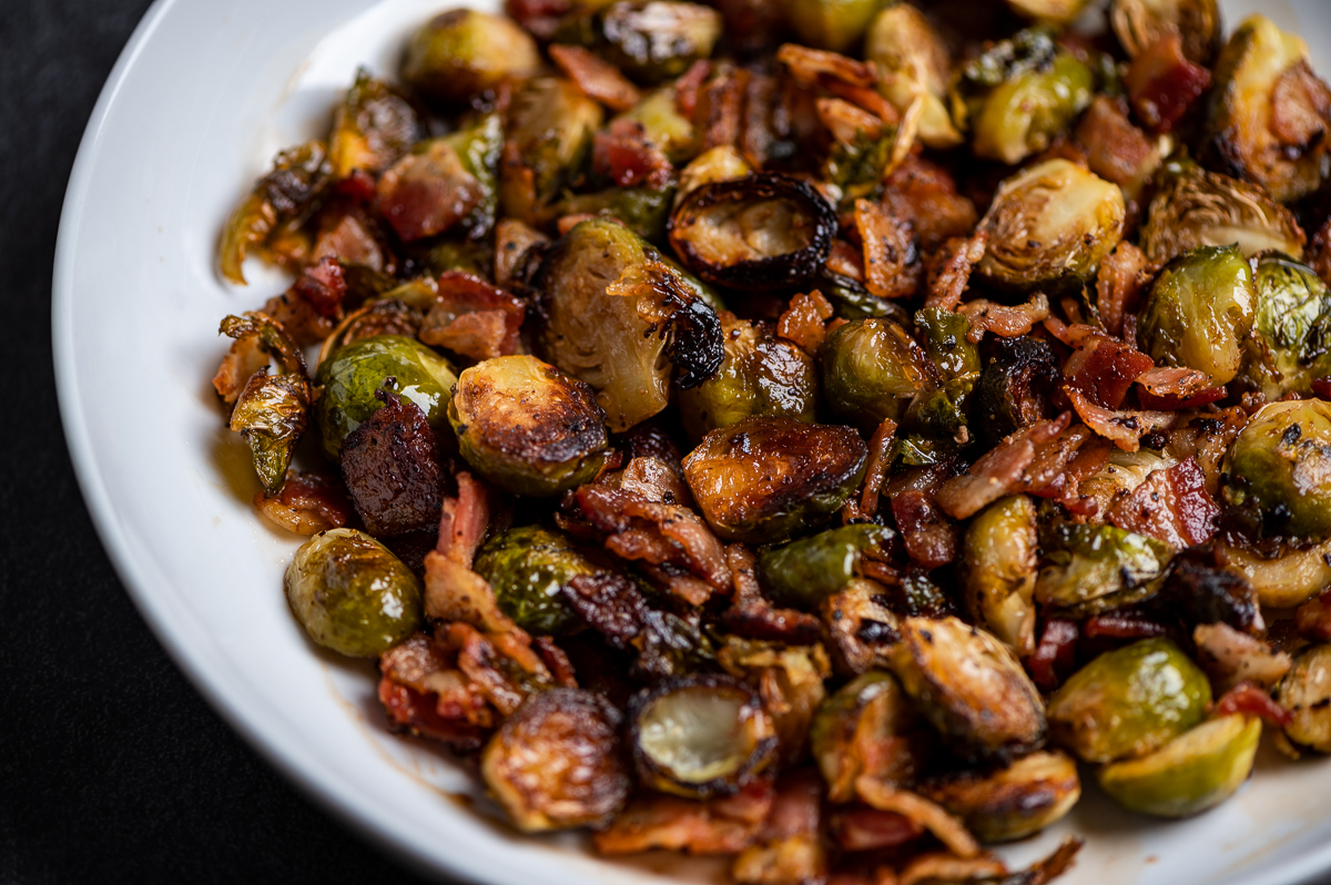 A closeup of a dish of roasted Brussels sprouts and bacon.