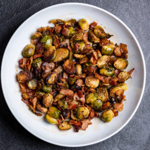 A white plate of roasted Brussels sprouts with bacon.