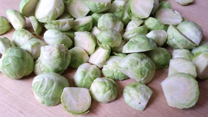 Brussels sprouts sliced in half on a cutting board.