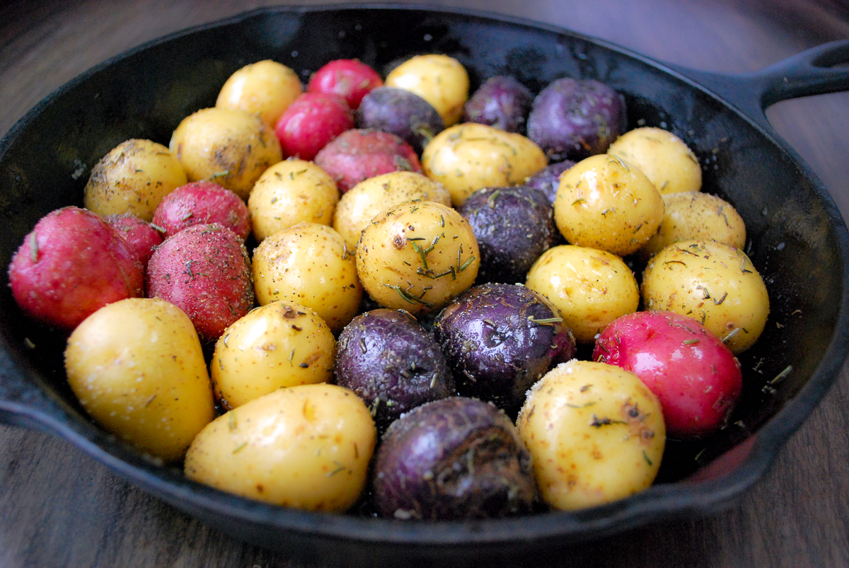 Baby colorful potatoes seasoned in a skillet.