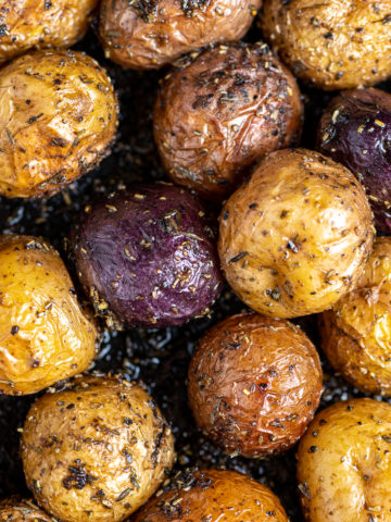 Roasted baby potatoes with rosemary and thyme in a cast iron skillet.