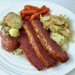 A plate of sliced corned beef, buttered potatoes, roasted carrots, and sautéed cabbage.