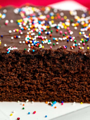 A slice of chocolate sheet cake topped with sprinkles.
