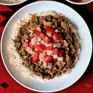 A plate of rice and lentils topped with tomato onion dressing.
