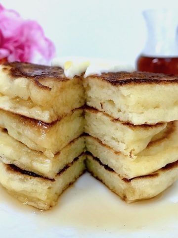 Stack of pancakes on a plate with syrup.