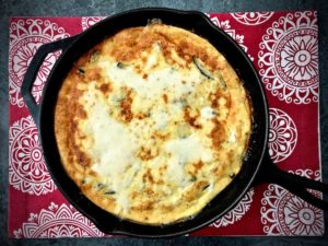 Baked zucchini frittata in a cast iron skillet.