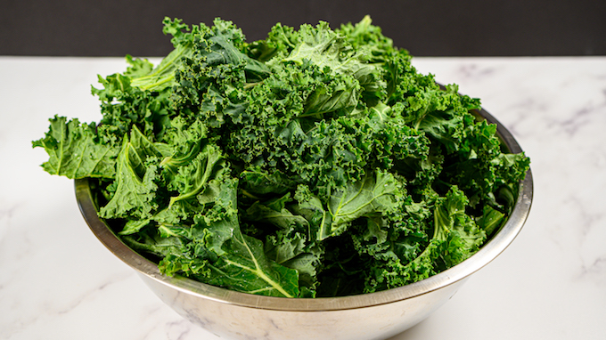 A big bowl of washed kale leaves.